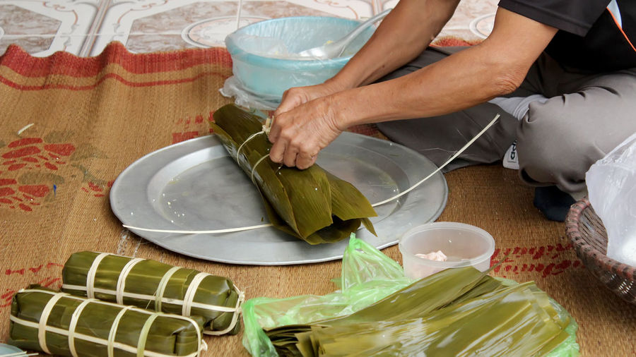 Low section of man packing food in leaves on tray