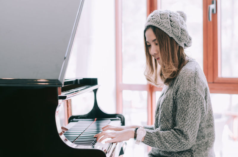 Beautiful woman playing piano and tone color. Music Arts Culture And Entertainment Beautiful Woman Casual Clothing Clothing Hair Hairstyle Hat Indoors  Leisure Activity Lifestyles Music Musical Equipment Musical Instrument Musician One Person Piano Real People Scarf Vintage Waist Up Warm Clothing Winter Young Adult Young Women
