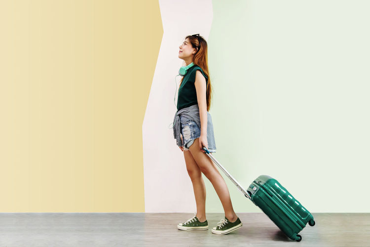 Full Length Side View Of Woman With Luggage Standing Against Wall
