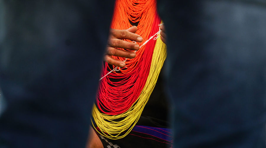 Cropped image of hands holding thread