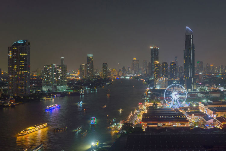 Ferris wheel at Chao Phraya River, Bangkok City, Thailand Asiatique The Riverfront Bangkok Chao Phaya River Ferris Wheel Thailand Architecture Boats Building Exterior Built Structure City Cityscape Development Ferris Wheel Financial District  Illuminated Modern Nautical Vessel Night No People Outdoors River Sky Skyscraper Tower Travel Destinations Urban Skyline Water Waterfront