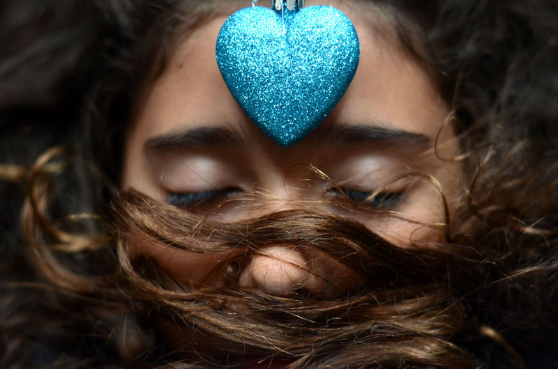 Close-up of woman with blue glitter heart on forehead