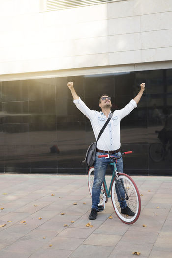 Mid adult man with bicycle standing against building