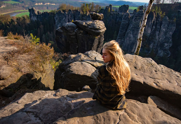 Young woman sitting on rock by mountains