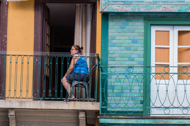Side view of woman sitting on table by railing