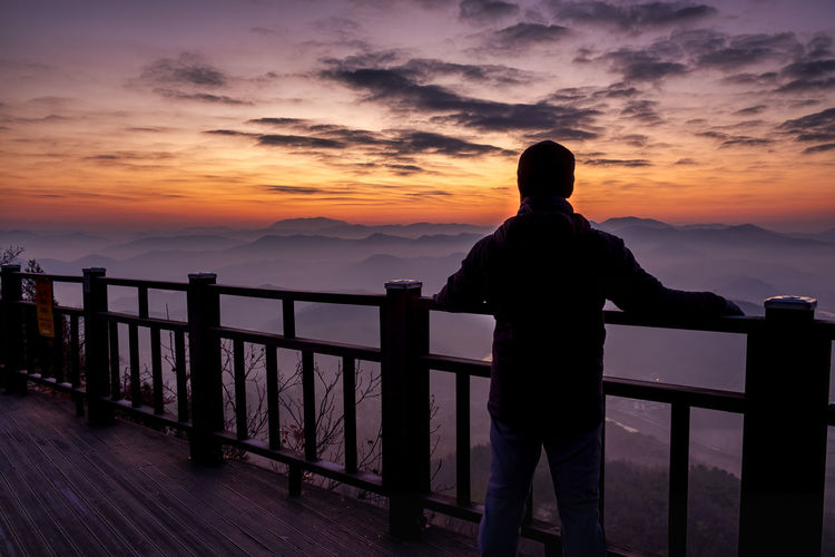 Rear view of silhouette man standing by railing against sky during sunset