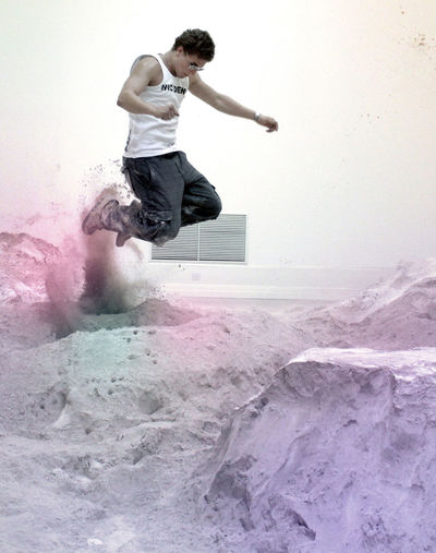 Young man jumping on pile of sand against wall
