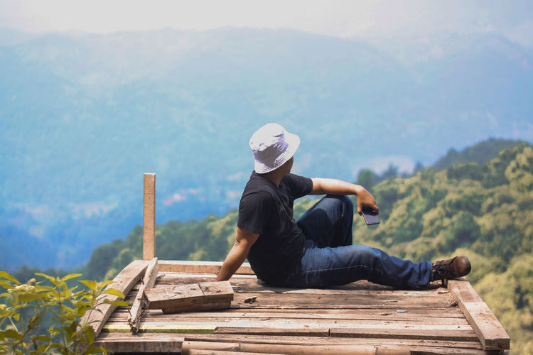 Man sitting on bench against mountains