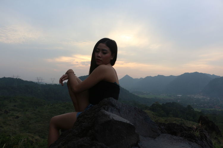 Young woman sitting on rock against sky during sunset