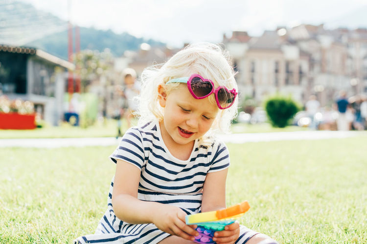A little blonde girl sitting on the lawn plays with a trendy toy pop it.