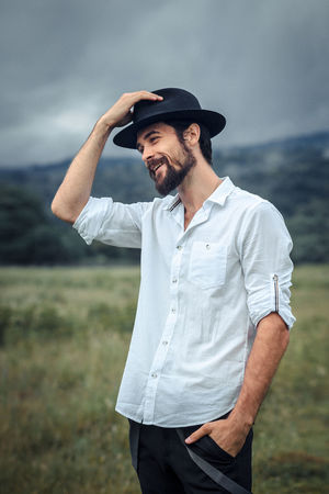 A handsome young man. Photo on nature. The guy wears a beard and medium length hair. He has an attractive face and a slim body. The man wears a black hat, a white shirt and trousers. Photo taken with daylight on a cloudy day in a mountainous area in the Caucasus. Green meadows and sky with clouds in the background. Freedom Hat Lifestyle Natural Beard Casual Clothing Clothing Countryside Field Focus On Foreground Front View Fully Unbuttoned Hat Leisure Activity Lifestyles Male One Person Outdoors Portrait Real People Standing Three Quarter Length Waist Up Young Adult Young Men