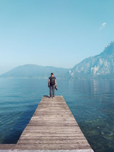 Man Photographer Travel Blue Water Lake A New Beginning Water Mountain Full Length Clear Sky Lake Politics And Government Blue Adventure Sky Landscape Horizon Over Water Fishing Rod Wave Fishing Surfer