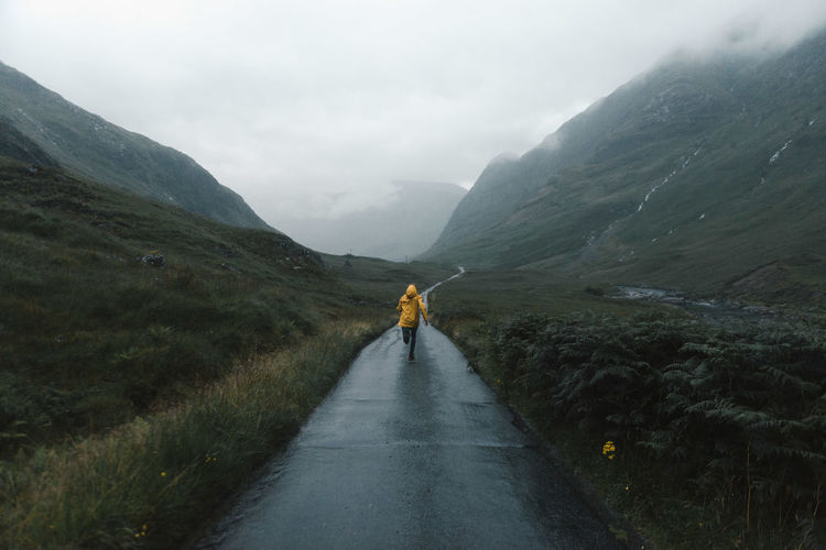 Rear view of woman running on country road in the scottish highlands