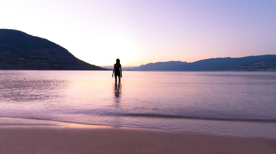 Rear view of woman standing at beach against clear sky during sunset