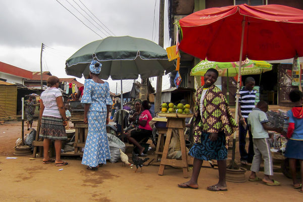 Nigerian girl smiling in a market stall African Happy Market Nigeria Africa Black Casual Clothing Girl Market Market Stall Nigerian Nigerians Outdoors People Real People Small Business Smile Stall Standing Umbrella Women