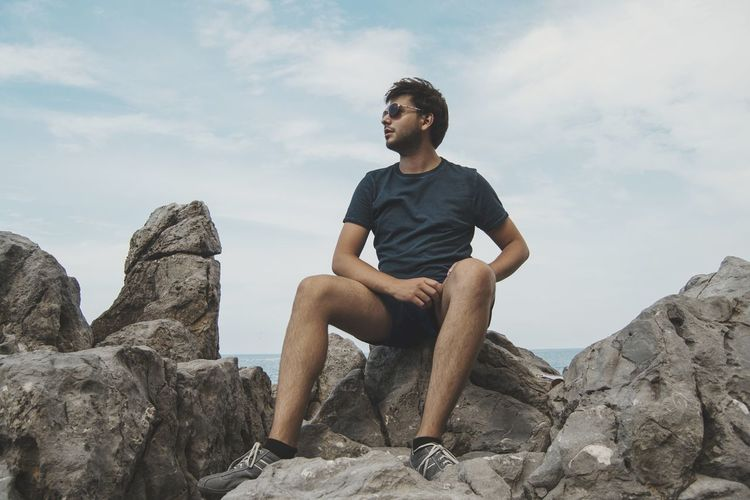 Full length of young man sitting on rocks at beach against sky