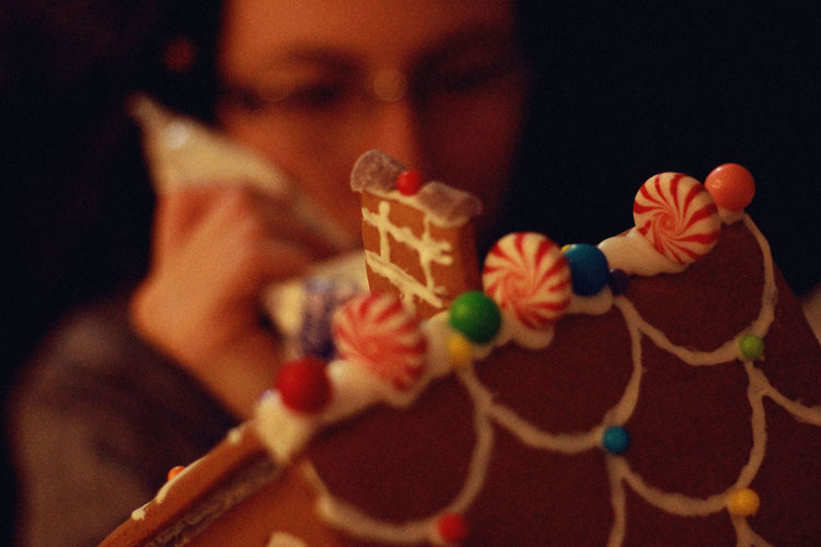 Close-up of woman icing on cake at home