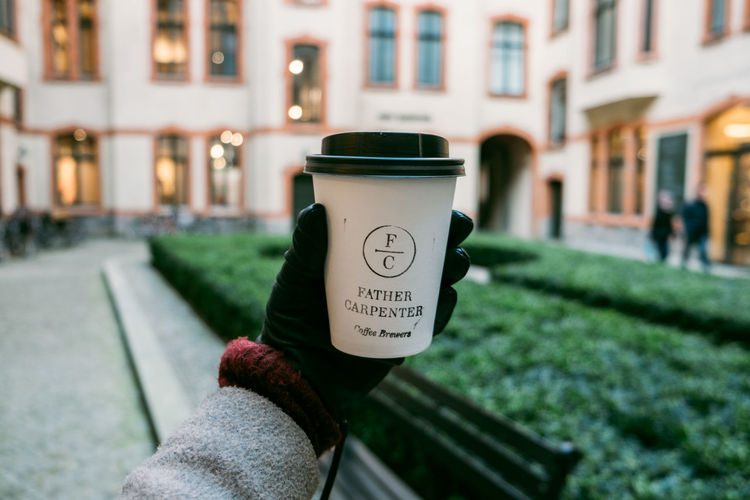 Coffee Architecture Brewery Building Exterior Built Structure City Coffee - Drink Coffee Cup Communication Cup Day Focus On Foreground Hand Holding Human Body Part Human Hand Lifestyles One Person Outdoors Personal Perspective Real People Street Text Unrecognizable Person Western Script