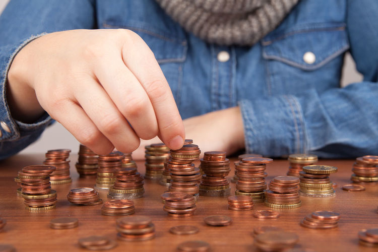 Midsection Of Woman Stacking Coins At Table