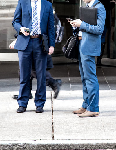 Low section of businessmen using mobile phones while standing on footpath