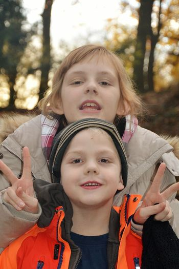Portrait Of Siblings Gesturing Peace Sign At Park During Sunset