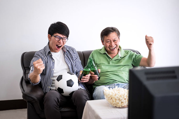 Friends With Clenched Fist Watching Soccer On Tv