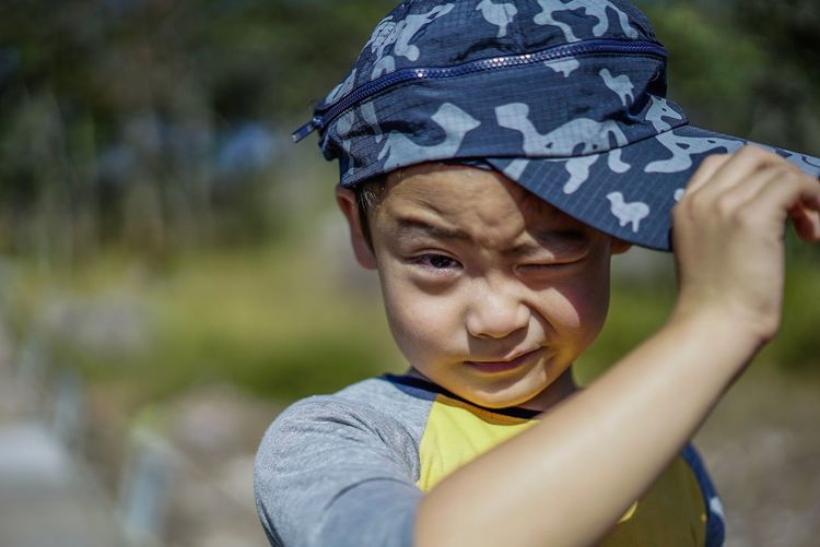 Close-Up Portrait Of Boy Winking While Wearing Cap Outdoors