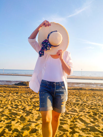 Rear view of woman wearing hat at beach against sky