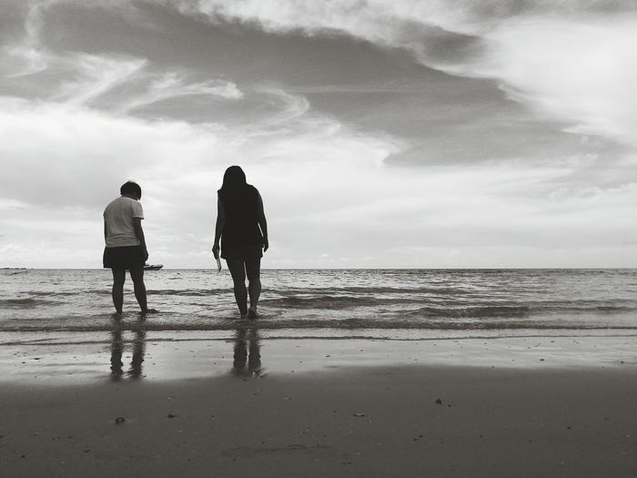 Rear View Of Women Standing At Beach Against Sky