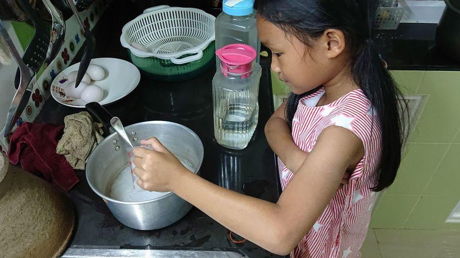 Side view of cute girl preparing food in kitchen