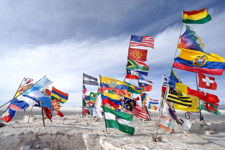 Colorful flags on rock against cloudy sky