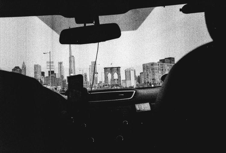 Silhouette buildings seen through car windshield