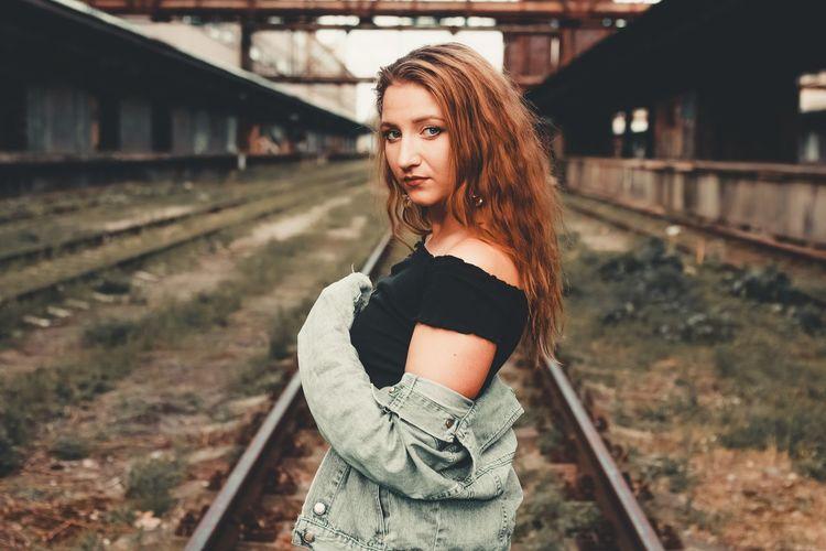 Portrait of beautiful woman standing on railroad track