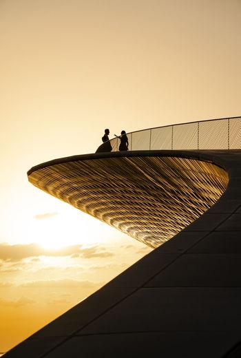 Silhouette people standing against orange sky