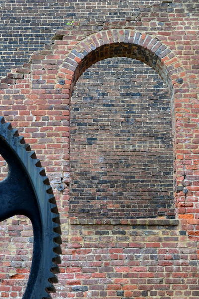 Arched opening with iron gear Arched Architecture Brick Brick Wall Building Exterior Built Structure Day Gear Geometry Ironwork  Metal Old Wall - Building Feature