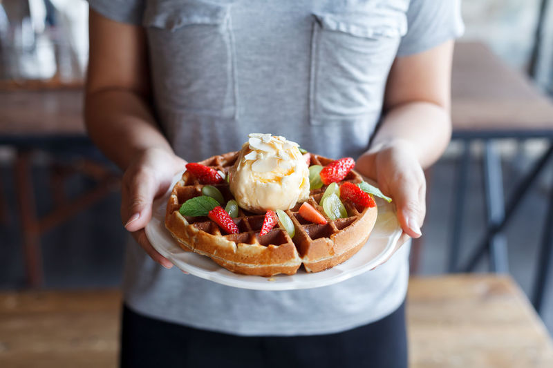 Midsection of woman holding waffle
