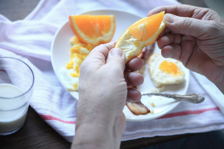 Man has fresh orange with breakfast Bacon Biscuit Breakfast Citrus  Dish Towel Drink Eating Eggs Fingers Food And Drink Fork Glass Of Milk Hands Holding Man Meal Natural Light Orange Pieces Oranges Personal Perspective Plate POV Textures