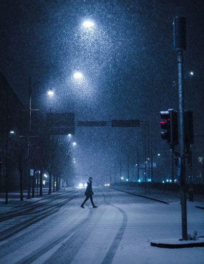 Man on city street during winter at night