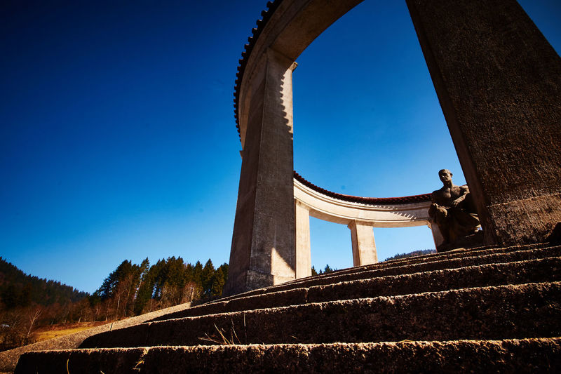 Low angle view of memorial against clear blue sky