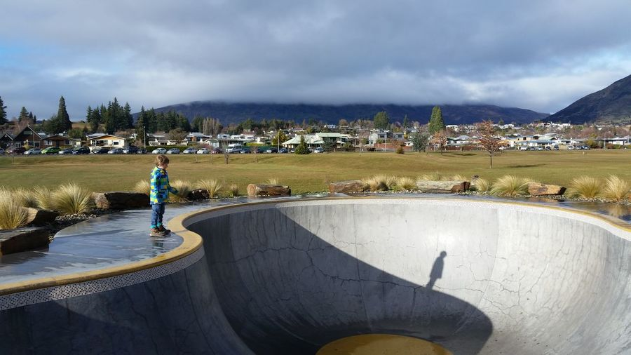 Full Length Of Boy Standing By Skateboard Park Against Cloudy Sky