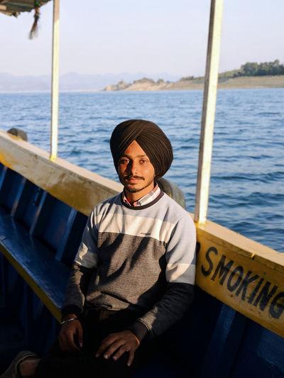 Portrait of man sitting in boat against sea