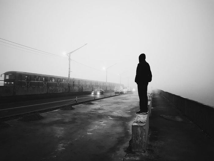 Full length of man standing on retaining wall at roadside in foggy weather