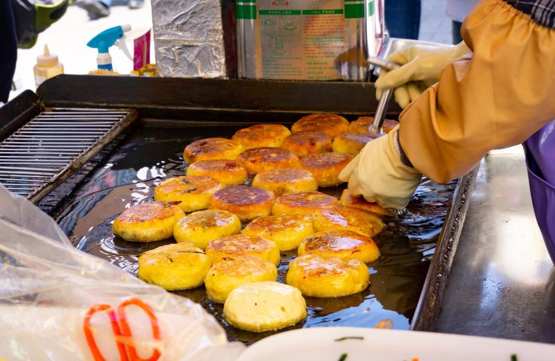 Person preparing food for sale at market stall