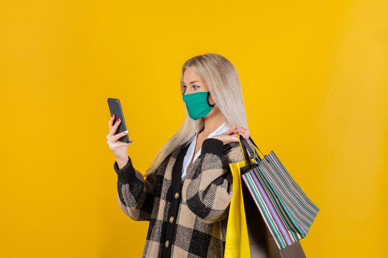 Young woman wearing mask using mobile phone against yellow background