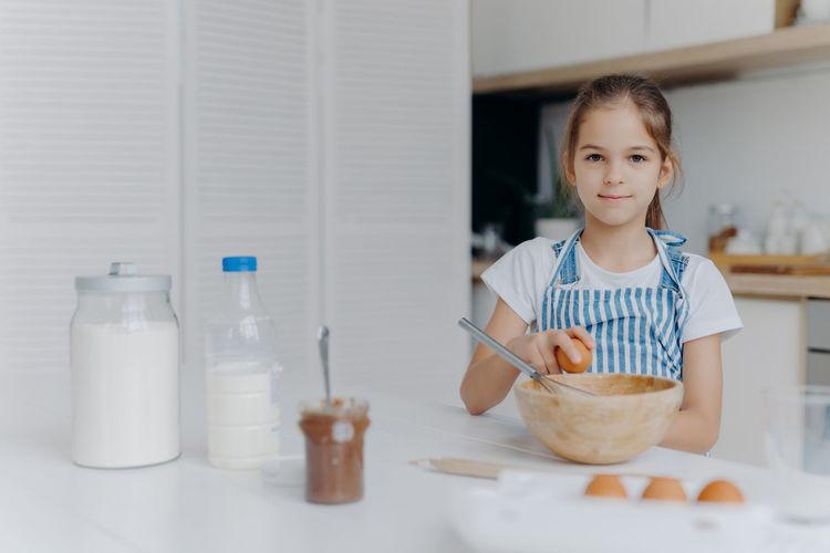 Portrait of girl breaking eggs in bowl on kitchen island