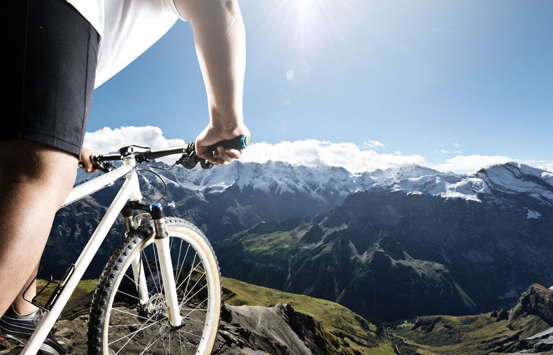 Low section of man with bicycle on mountain against sky