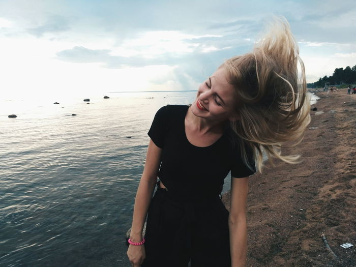 Beautiful woman tossing hair while standing at beach
