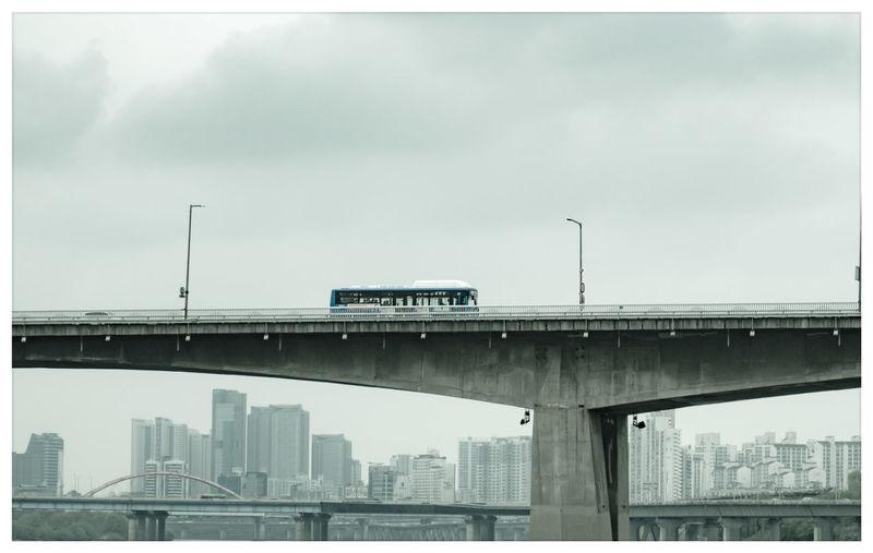 Bridge over cityscape against sky