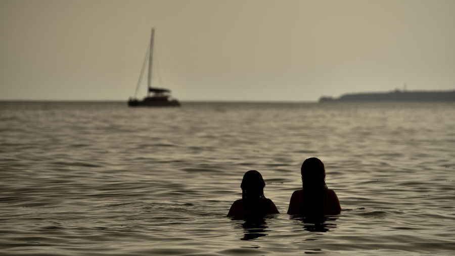 Silhouette women swimming in sea against sky during sunset