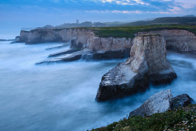 Scenic view of cliffs by sea at shark fin cove beach
